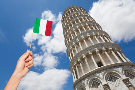 Hand with Italian flag against the Tower of Pisa