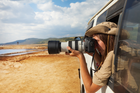 Girl taking photo of African savannah from jeep