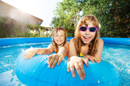 Dos niñas felices nadando en la piscina en un día soleado