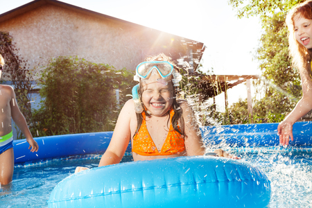 Niños felices jugando en el agua azul de la piscina