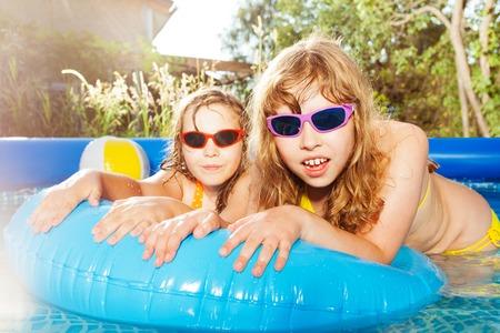 Deux filles nageant dans la piscine avec bouée