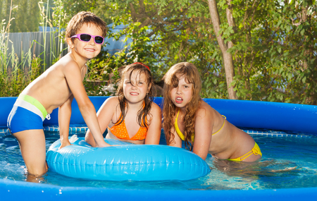 Three happy kids having fun at tub in the yard Standard-Bild