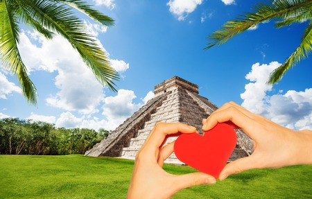 Hand hold red heart in Chichen Itza pyramid Mexico