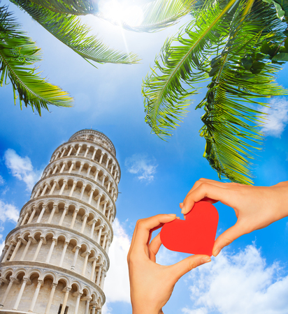 Hand hold red heart over leaning tower in Pisa