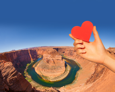Hand hold red heart and horse shoe canyon colorado Фото со стока