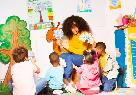 Nauczycielka w przedszkolu pokazuje karty pogodowe