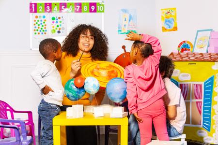 Diverse kids group learn planets in nursery school