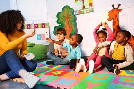 Muchos niños en el jardín de infantes juegan con el maestro. Foto de archivo