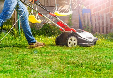 Lawn mower man using walk behind lawnmower 写真素材