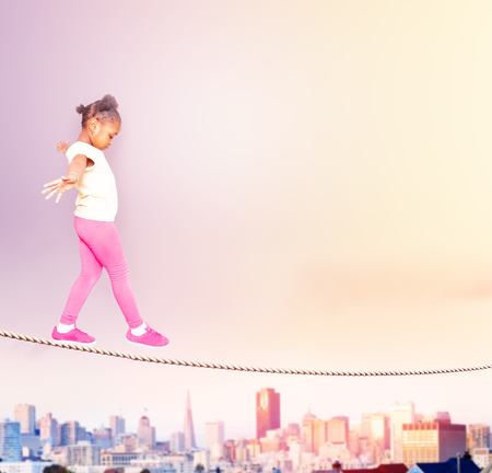 Beautiful black girl walking on the rope over city