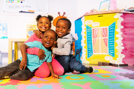 Laughing group of kids play on the floor in room Stock Photo