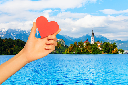 Red love heart and on church on the small island in the middle of the Bled lake, symbol of Slovenia with Alp mountains on background
