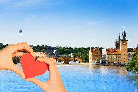 Red love heart and on background Charles Bridge crossing blue river in Prague, Czech Republic