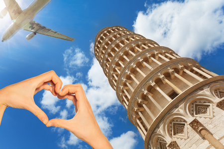 Red love heart and on background Pisa tower, airplane with tourists passing by