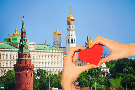 Red love heart, on background view with Cathedral of the Annunciation, Vodovzvodnaya tower and Grand Kremlin Palace in summer in Moscow, Russia