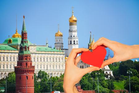 Rotes Liebesherz, im Hintergrund mit der Kathedrale der Verkündigung, dem Vodovzvodnaya-Turm und dem Großen Kremlpalast im Sommer in Moskau, Russland Standard-Bild