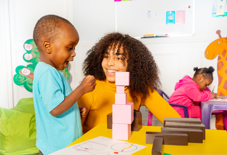 Excited little boy in nursery about block tower Stock Photo