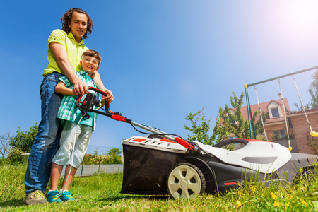 Father teaching son edging the lawn with lawnmower Stock Photo