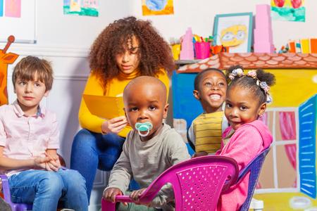 Bambino con ciuccio nel gruppo asilo nido per bambini