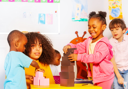 Small group diverse kids build tower with block Stock Photo