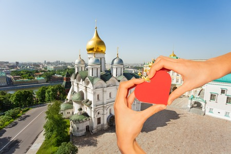 Hand hold red heart over churches, Moscow Kremlin