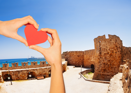 Red love heart and on background court of the Knights Grand Master Palace with Aegean sea waterscape, Rhodes Island, Greece