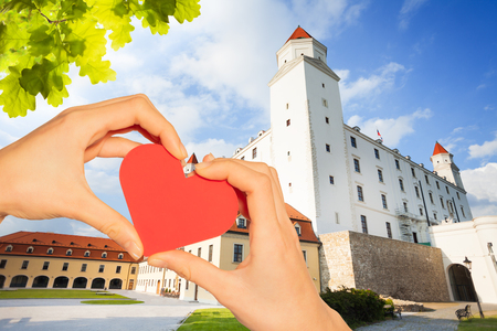 Hand hold red heart over Castle yard in Bratislava