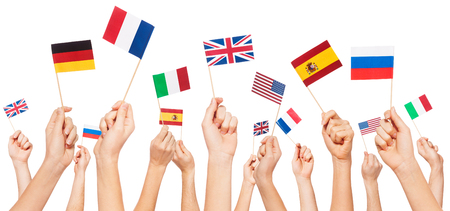 Hands holding flags of USA and EU member-states Фото со стока