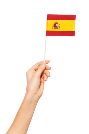 Hand holding the national flag of Spain by pole