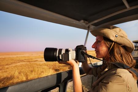 Woman taking photo aboard safari jeep at savannah