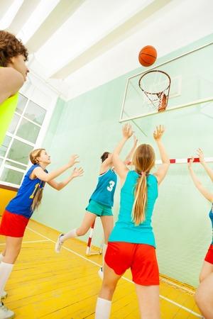 Tienermeisjes in sportuniform die basketbal spelen Stockfoto