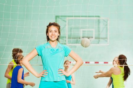 Feliz chica asiática, miembro del equipo de voleibol, en el gimnasio Foto de archivo