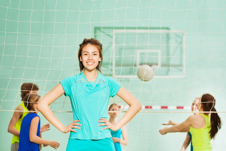 Happy Asian girl, volleyball team member, in gym