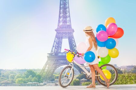 Girl cycling through Paris with colorful balloons Zdjęcie Seryjne