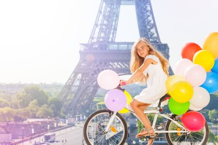 Girl cycling through Paris with balloons bouquet