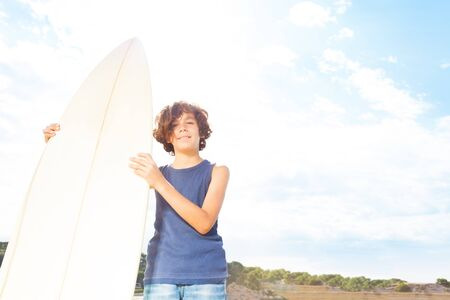 Boy with surf board stand on the beach