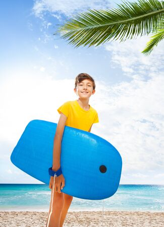 Cute portrait of kid with body board on palm beach Imagens