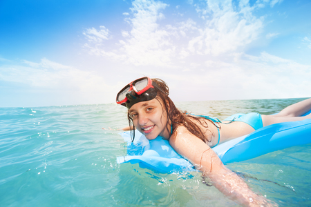 Cute teen girl snorkeling on matrass in the sea