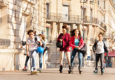 Big group of teenagers with inline skates and skateboard riding along the streets at sunny day
