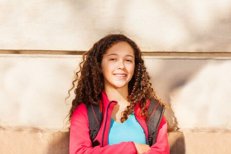 Teenage curly-haired girl with backpack outdoors