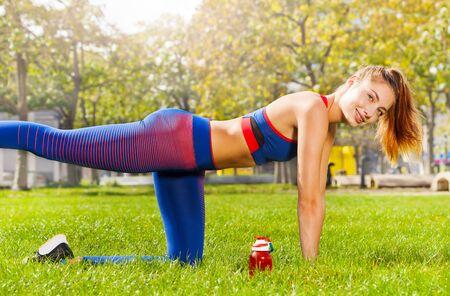 Junge Frau, die sich im Freien beim Beinschaukel ausdehnt Standard-Bild