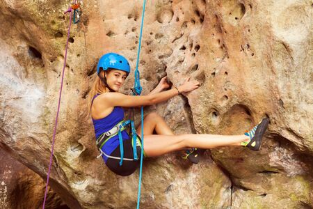 Woman rock climbing on a very difficult route Stock Photo
