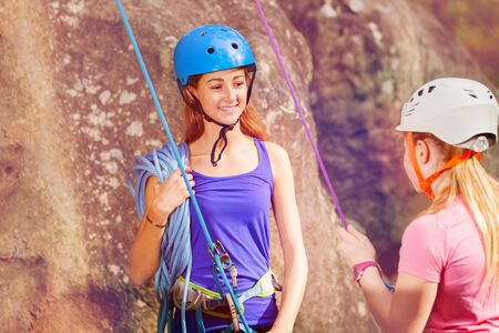 Female coach with girl preparing to rock climbing