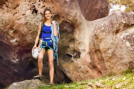 Girl standing with rock climbing equipment