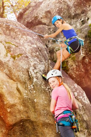 Girl training rock climbing with instructor Stock Photo
