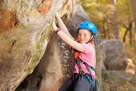 Young mountaineer training rock climbing outdoors