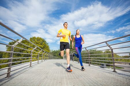 Young fitness couple running outdoors