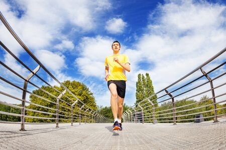 Man running sprinting across the bridge outdoors