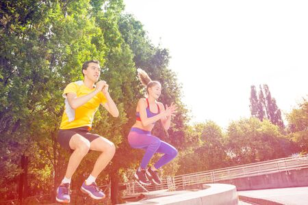 Active people doing box jump exercise outdoors
