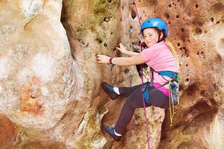 Teen girl rock climbing on a very difficult route